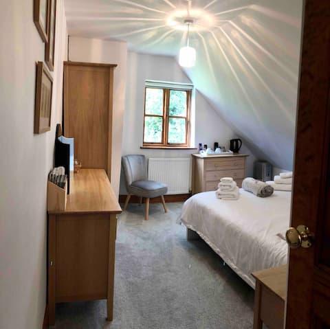 Habitación doble del dormitorio de la casa del país TV y baño grande