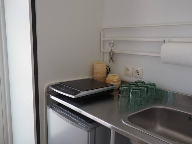 kitchenette with fridge under counter and single eye hob for cooking.  note: discreet closet space next to it
