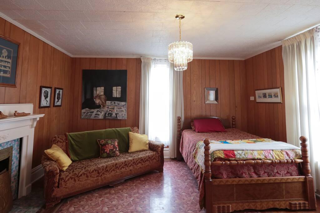 One bedroom upstairs has an antique sleeper sofa and 1950's linolelum rug