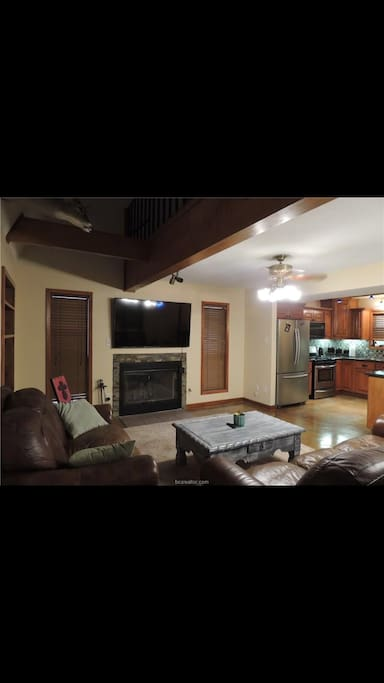 """Nice view of a 65"""" flat screen with two couches."""