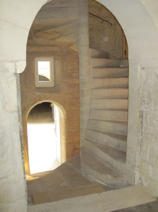 Spiral staircase - the heart of the house with ten levels - looking from the dining area out to the courtyard
