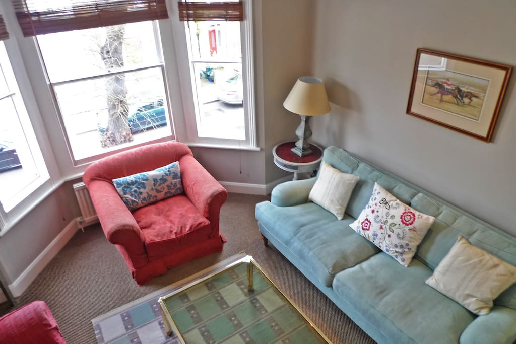 Cosy sitting room with TV and lovely big windows
