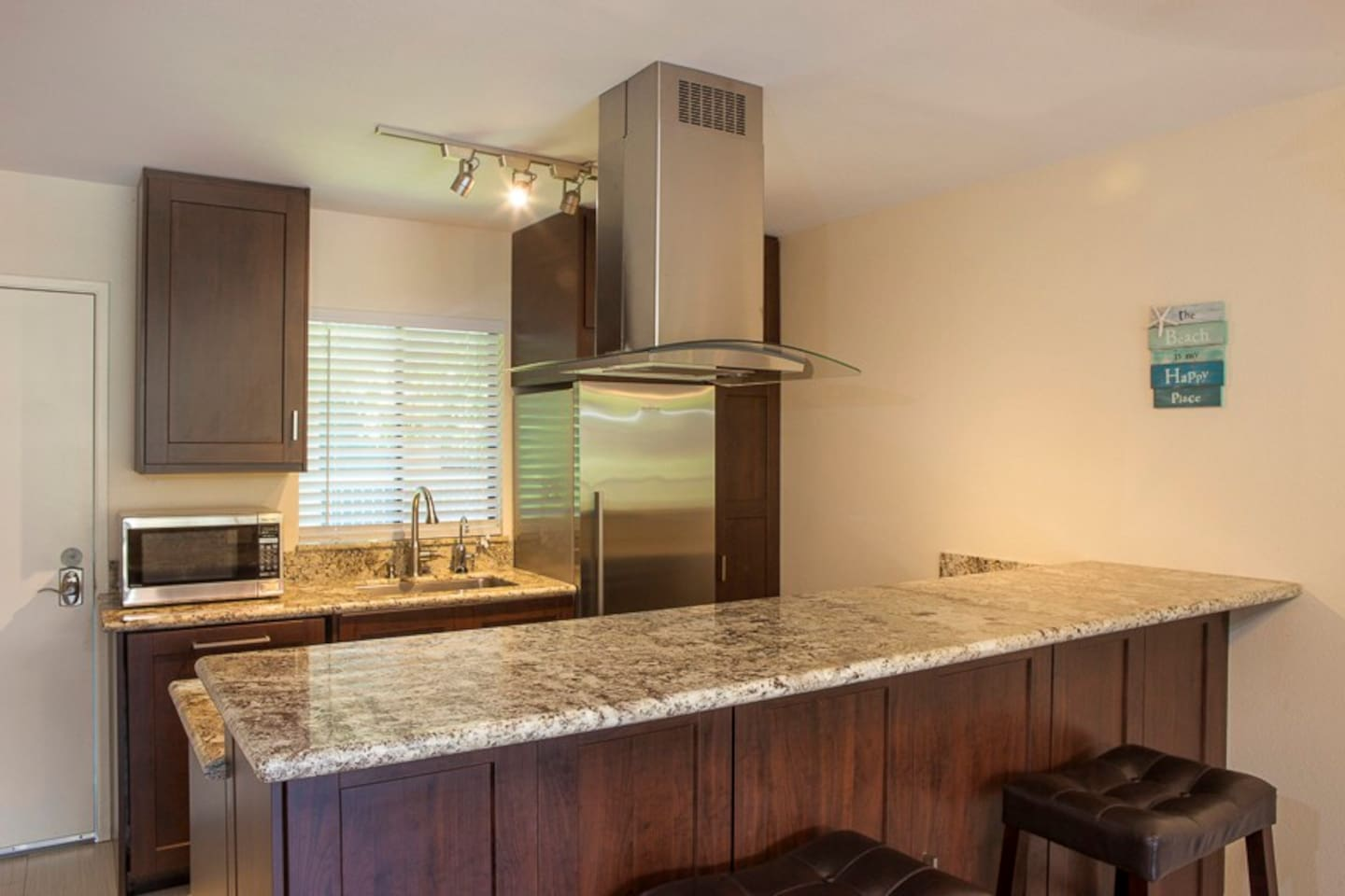 Completely remodeled Kitchen, with a counter and bar stools.