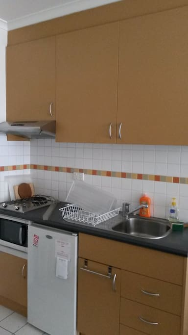 Kitchen with fridge, microwave, gas stove top, kettle, utensils and crockery