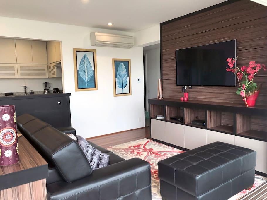 Sala de estar aconchegante, com sofás em couro e ar condicionado