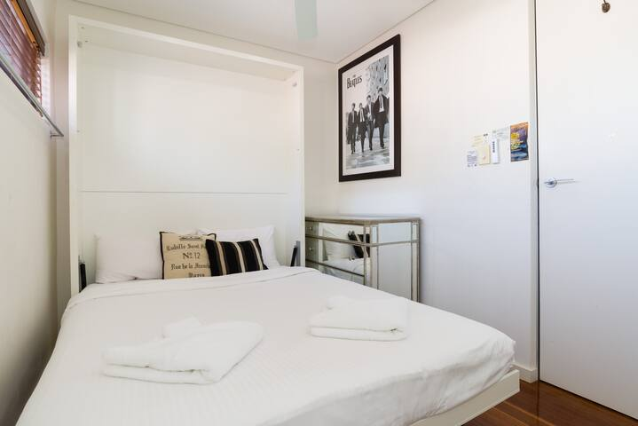 In the second bedroom, the comfortable bed is  fitted with hotel-style linens to ensure a good night's sleep.