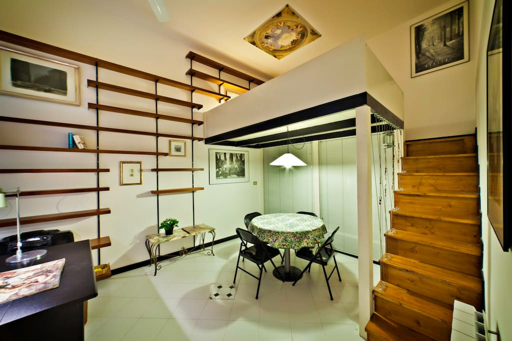 The dining space with the elegant stairs leading to the trendy loft-style bedroom.