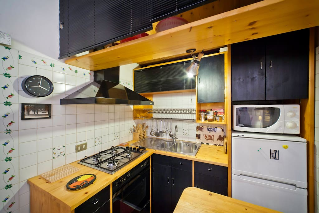 The kitchen is fully functional and is complete with pans, pots, vent hood, microwave and accessories