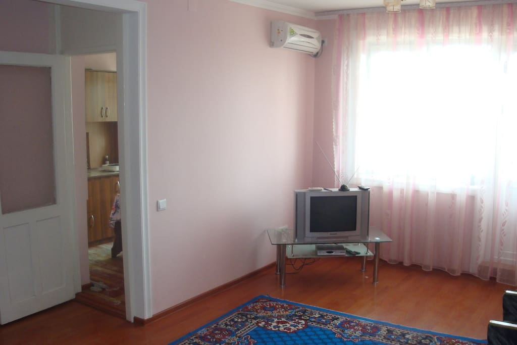 big room with AC, TV/satelite, armchairs with a coffee table and a foldable couch