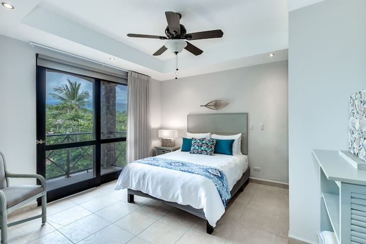 Second bedroom with queen bed and balcony access.