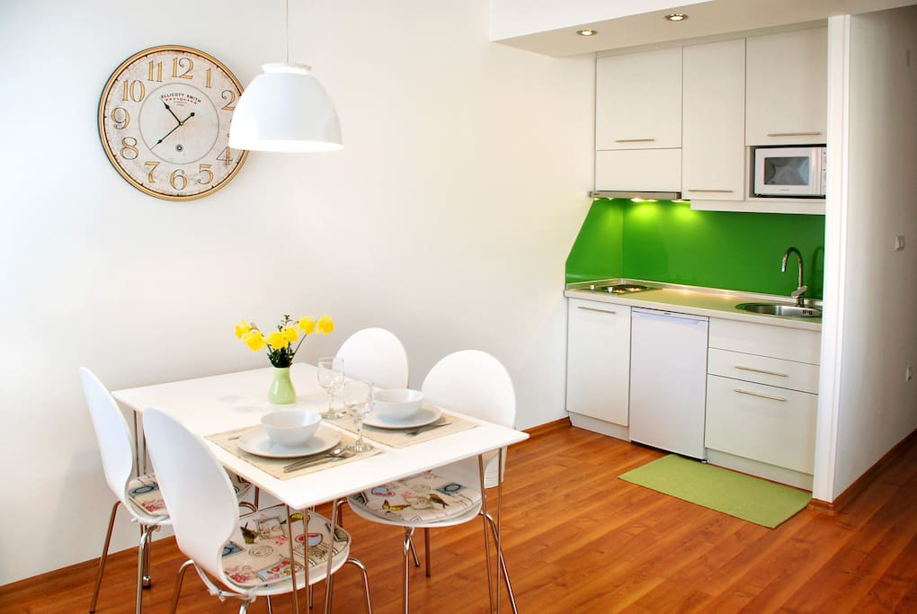 Dining table conveniently next to well-equipped kitchen with food basics included