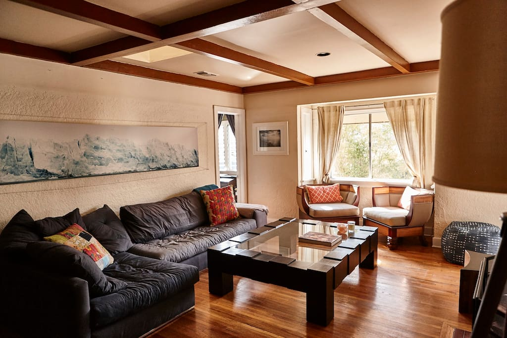 Living room with large comfy couch, fireplace, flat screen and views.