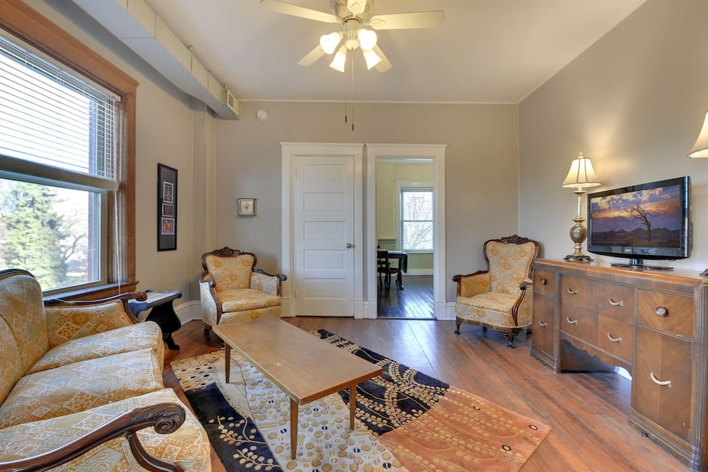 Living room with view of kitchen entrance on right and smaller bedroom door with full sized bed on the left. Spacious for your Super Bowl LII crew!