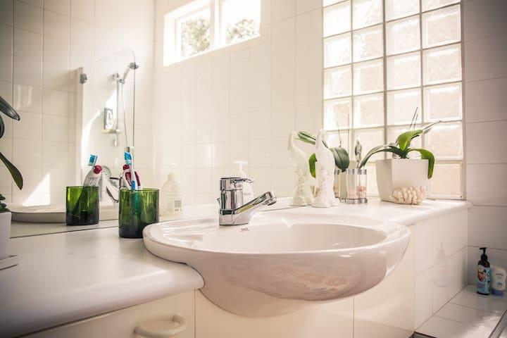 Guest Bathroom, vanity, toilet and shower over bath,
