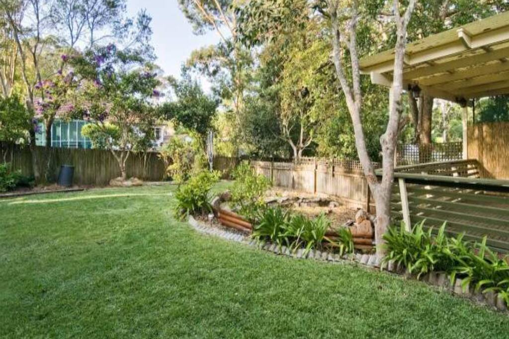 Large, leafy sunny garden and deck