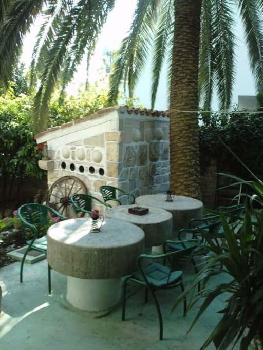 STONE ANTIQUE TABLES ON A SPACIOUS TERRACE UNDER THE PALM TREES