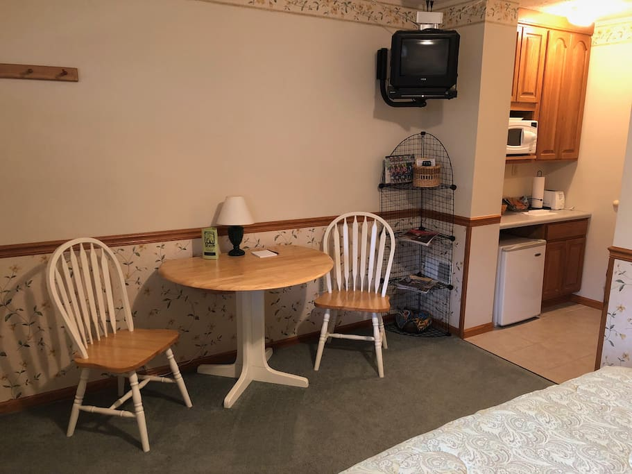 A small kitchenette with a table a chairs.