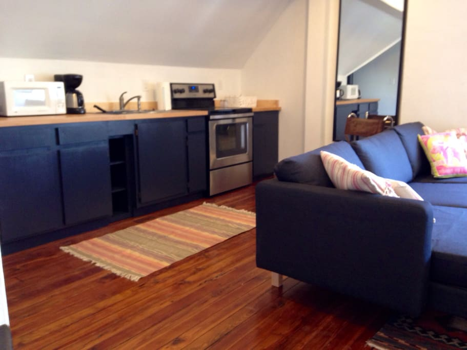 Kitchen Space featuring oven, coffee maker, microwave, pots/pans and a full set of flatware.