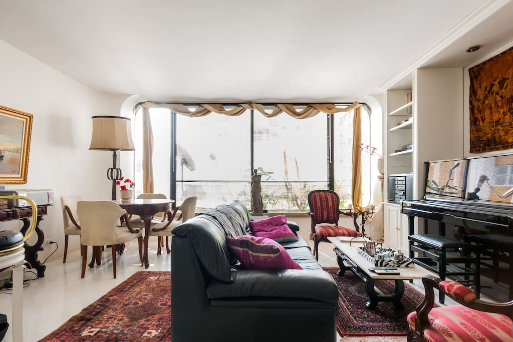 Bright gorgeous decor large living room with TV, games, bar and dinning area.