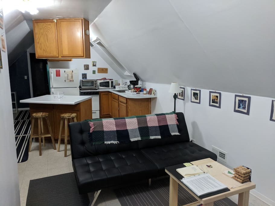 Front sitting area and kitchen. House manual and guidebook on the coffee table. Futon folds down into a bed for a 3rd guest.