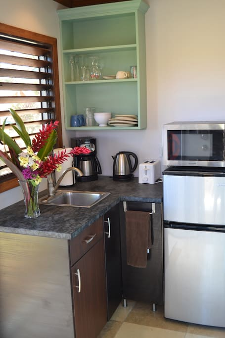 Small kitchenette -separate refrigerator and freezer, microwave, coffee maker, hot water heater, toaster, outdoor bbq grill, utensils, dishes, and more.