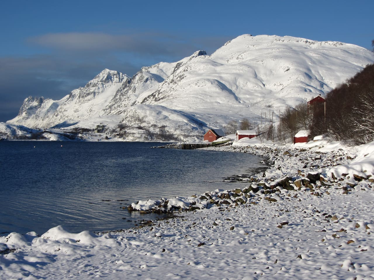 House and boathouse viewed from shore in late winter