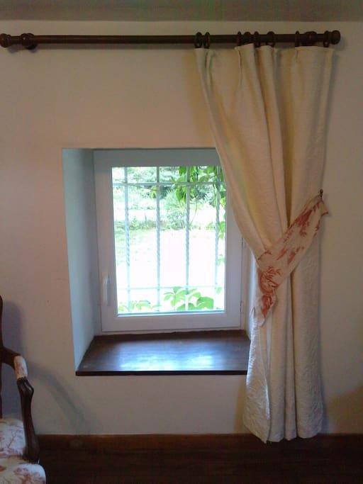 Fenêtre avec moustiquaire donnant sur le près