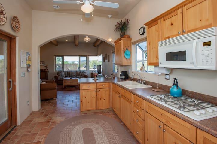 Kitchen with pine cabinets, garden window, sliding door to private courtyard.