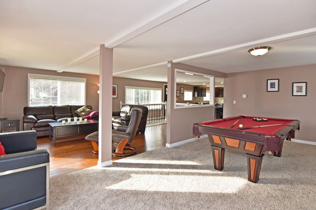 The living room is next to the game room in this open layout.