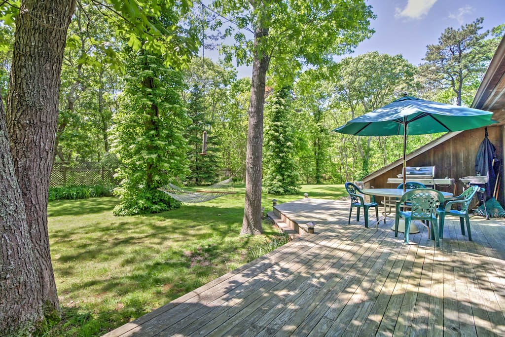 This home boasts a large deck, a cozy hammock, a vast yard and swimming pool.
