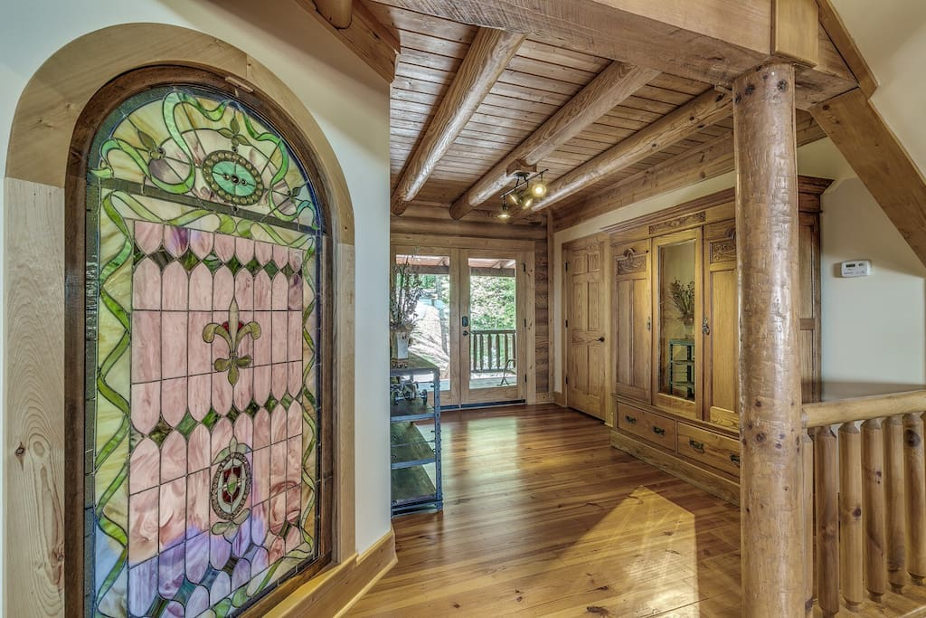 Gorgeous entry hall with antique armoire and custom framed antique stained glass.