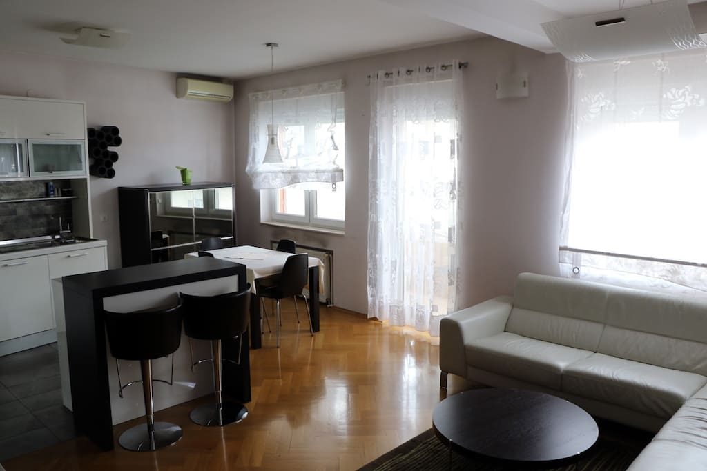 Spacious and light living room with big screen TV and AC