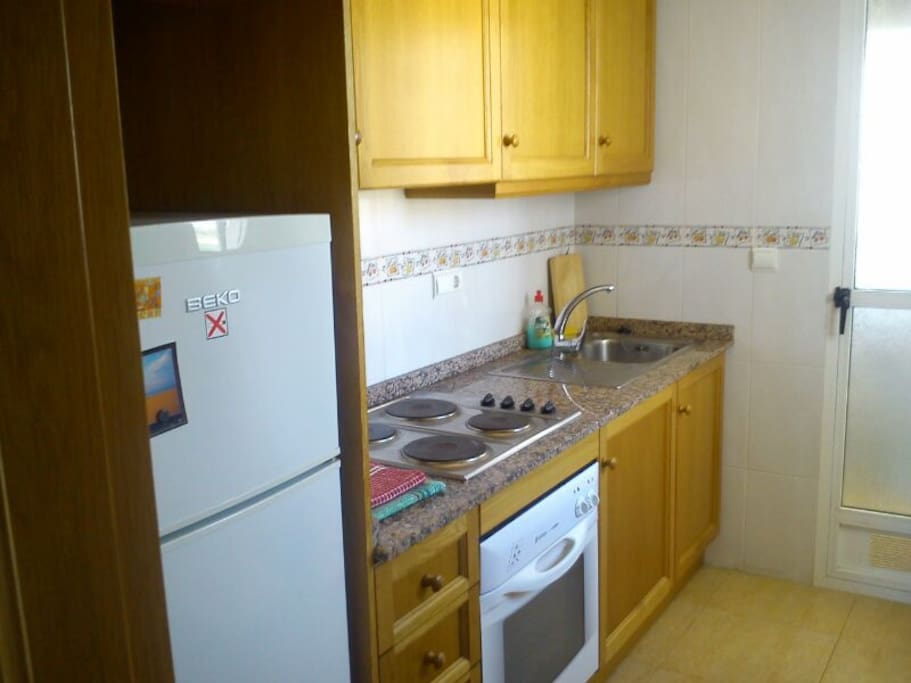 Kitchen with Fridge,Freezer, kettle, toaster and utensils. Utility Room out the back with washing machine