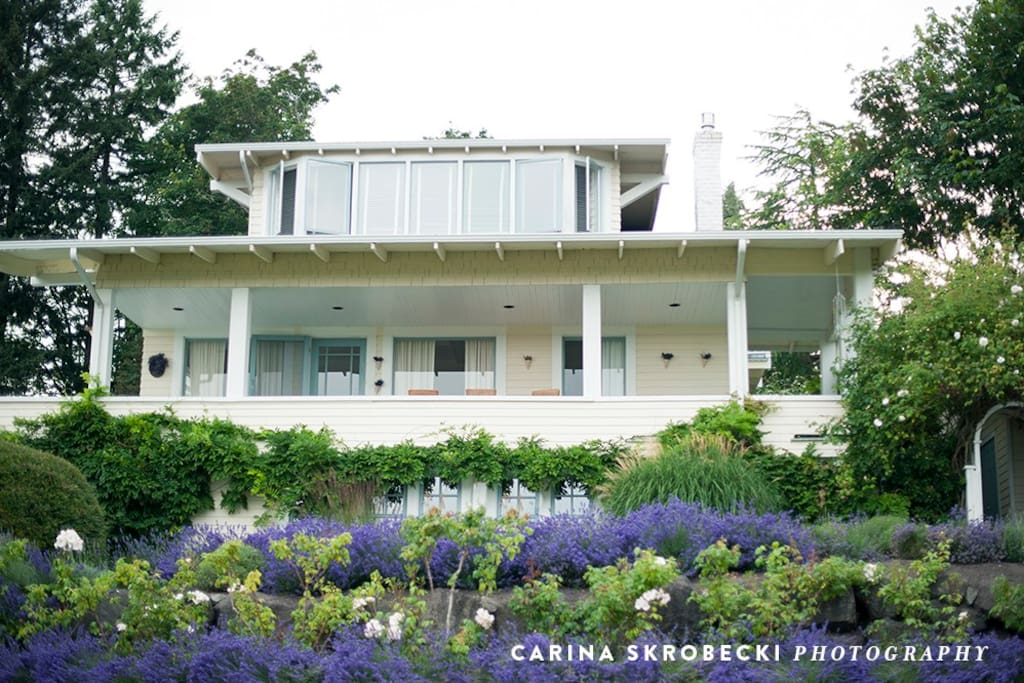 Welcoming front porch overlooks the lavender and harbor