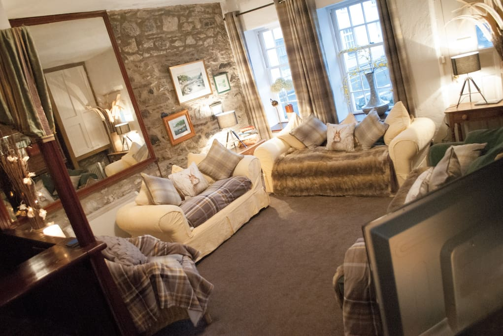 The sitting room, lots of throws, cushions, a flat screen TV, plus DVD player and video