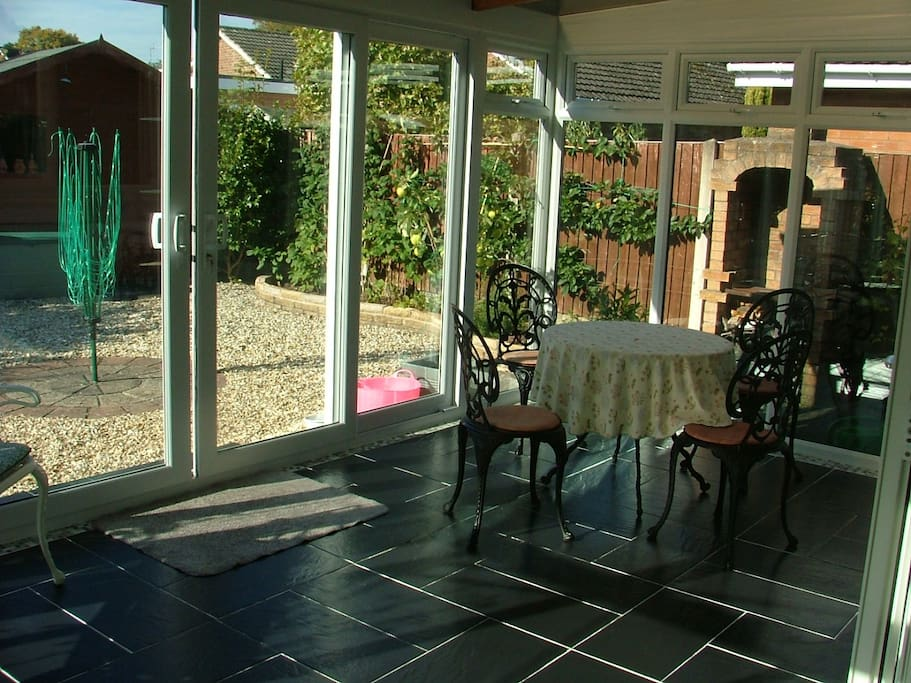 Open and warm conservatory, with extra eating space, usable throughout the year thanks to under floor heating.