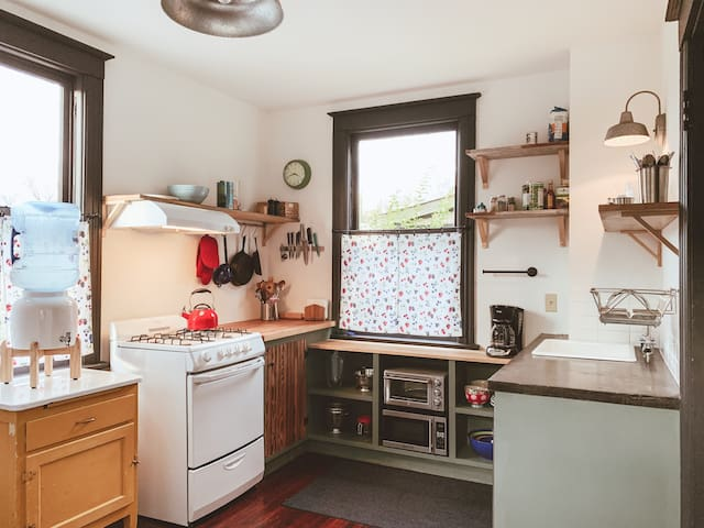 Kitchenette is tiny and functional with gas range, open shelving, concrete and butcher block countertops, mini-fridge, toaster oven and microwave. Under counter storage for mixer, bowels, pots and pans.