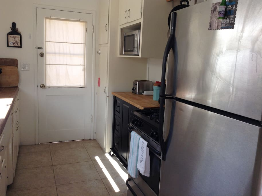 Kitchen with gas stove and refrigerator. Door takes you to washer and dryer