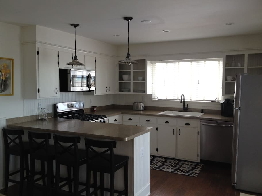 View into kitchen from living room.  Kitchen has 4 counter stools