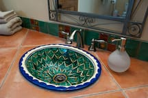 Bathroom décor includes tile floors and countertop, Mexican Talavera sink and accents.