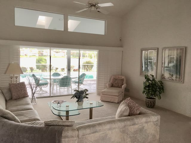 Family room/sitting room with plantation shutters and sliding glass doors that open onto lanai/pool