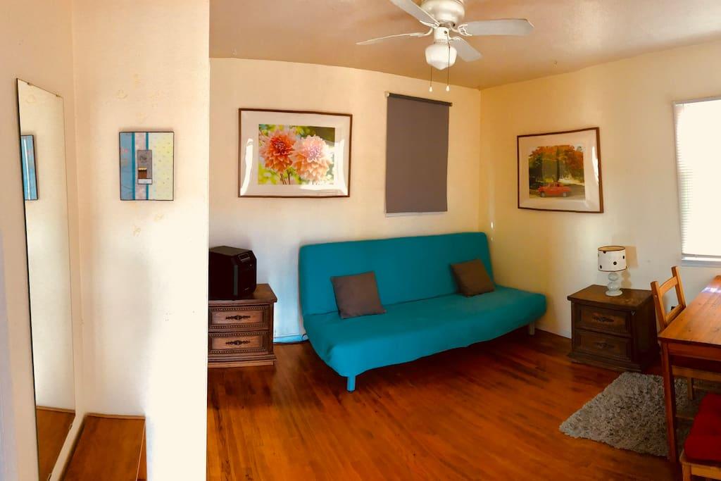 MAIN ROOM: Comfortable futon in sofa mode, window shade closed. Hardwood floor, table for desk or dining.