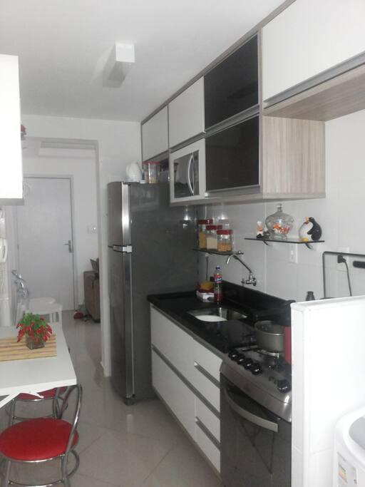 Cozinha com geladeira, microondas, fogão, liquidificador, mesa de apoio e dois banquinhos...