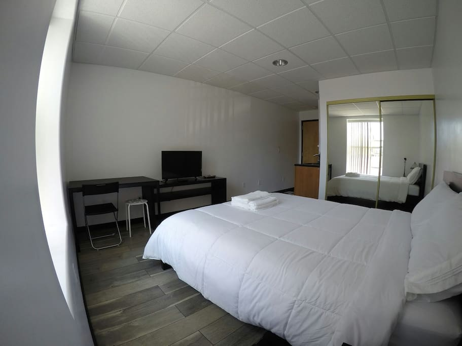 tv, wifi, private room with mini kitchenette, sliding mirror closet, table/ work area, and bathroom