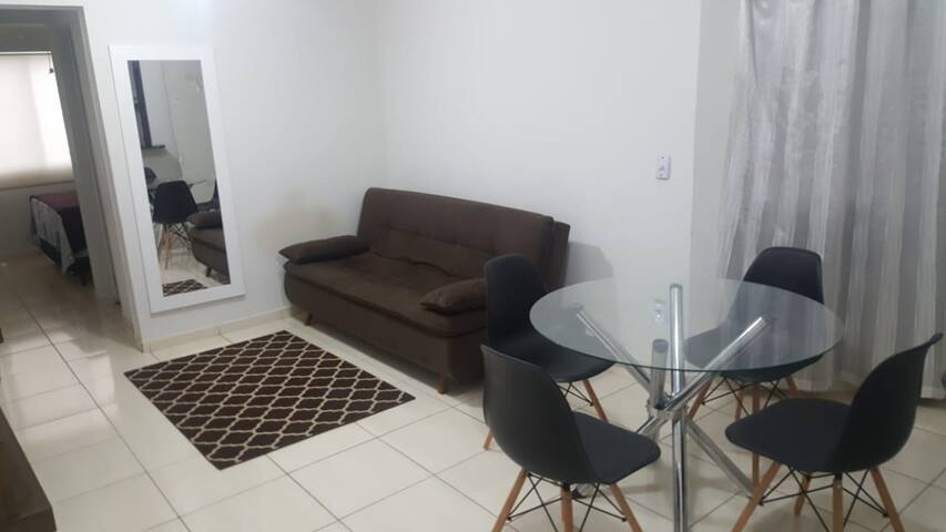 Sala de estar, com um sofá cama, mesa de jantar, com um rack para TV que possui NETFLIX