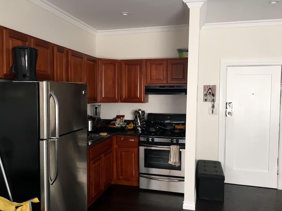 Kitchen: fridge, stove, wood cabinets, front door.