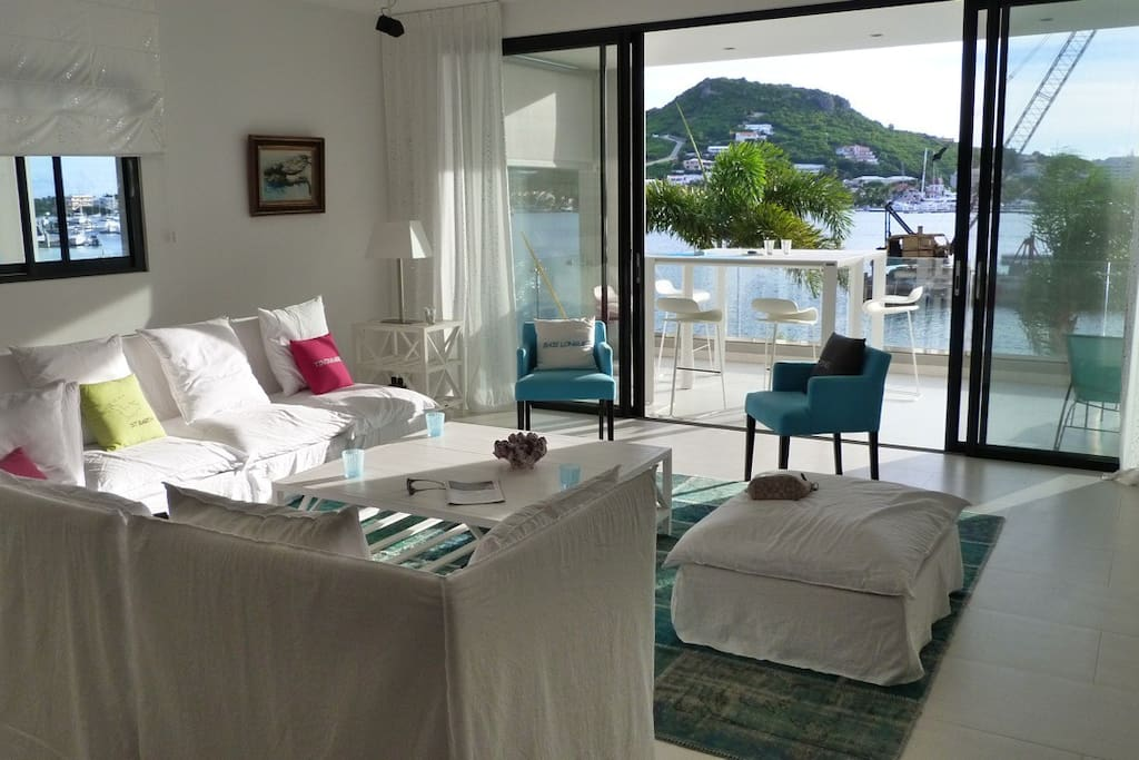 Living room area with a flat screen TV and view of the lagoon and sea