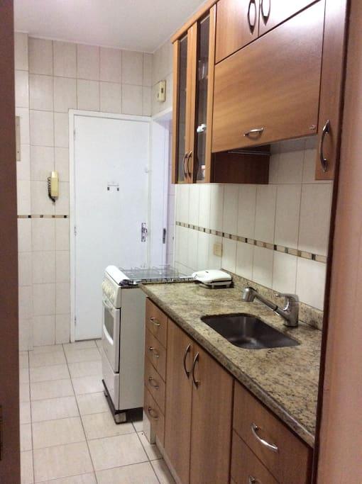 Cozinha com fogão, filtro para água, microondas e máquina de lavar roupa.