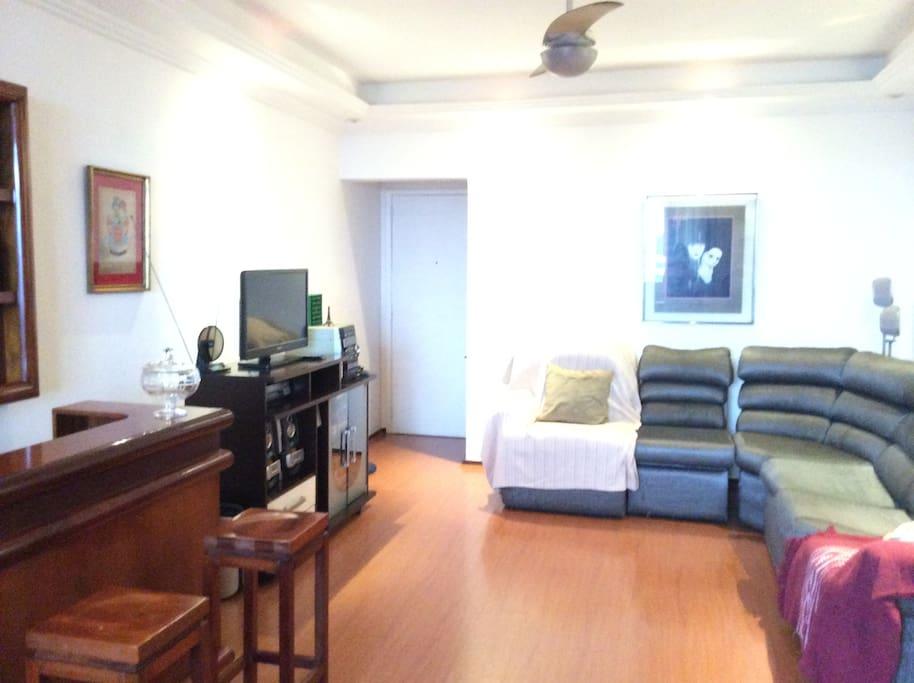 Ampla sala com sofá cama, rádio, TV e DVD.
