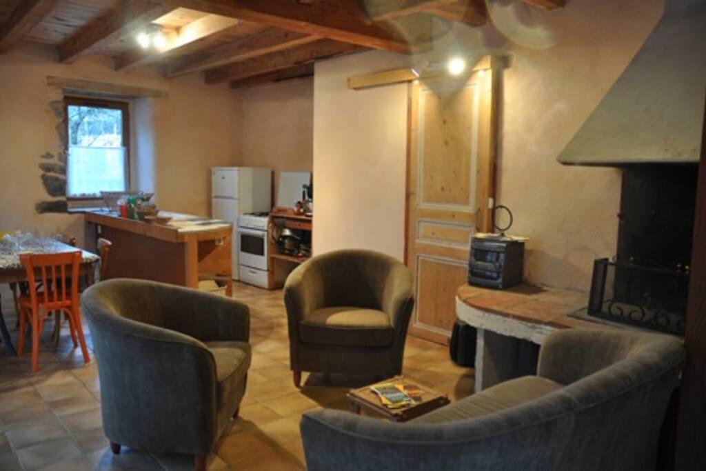 Vue d'ensemble de la pièce à vivre au rez-de chaussée (cuisine aménagée, salle à manger, salon et cheminée